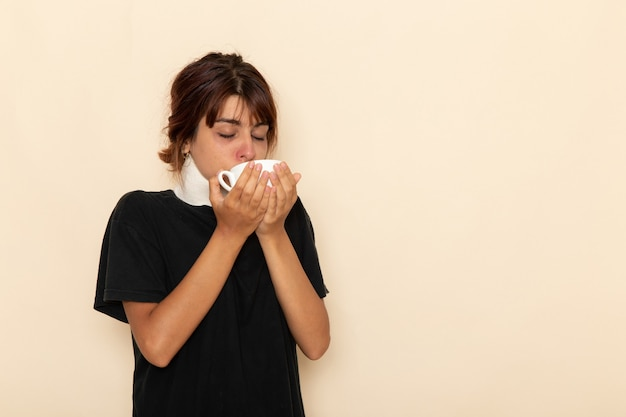 Vorderansicht kranke junge frau, die sich sehr krank fühlt und kräutertee auf weißer oberfläche trinkt