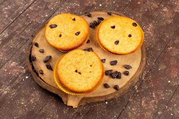 Vorderansicht kuchen mit schoko-häppchen auf dem braunen schreibtisch und holz rustikal