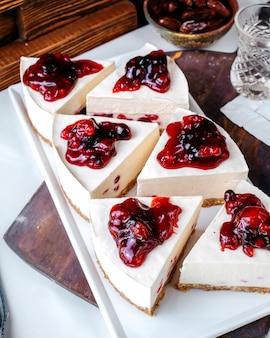 Vorderansicht kuchen schneidet kirschkuchenstücke innerhalb der weißen platte auf der hellen oberfläche