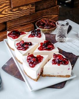 Vorderansicht kuchen schneidet leckere kirschkuchen in weißer platte auf dem hellen boden
