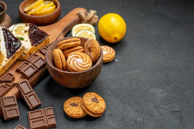 Vorderansicht kuchenscheiben mit keksen und schokolade auf dunklem hintergrund kuchen dessert kuchen süß