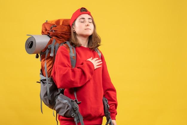 Vorderansicht kühlen weiblichen reisenden mit dem rucksack, der augen schließt, die hand auf ihre brust setzen