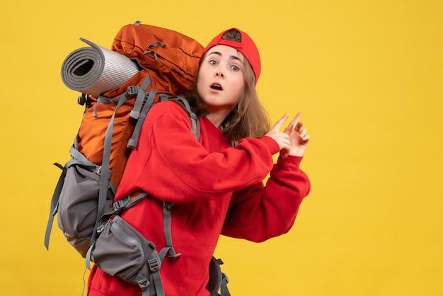Vorderansicht kühlen weiblichen reisenden mit dem rucksack, der finger nach hinten zeigt