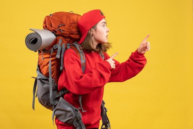 Vorderansicht kühlen weiblichen reisenden mit dem rucksack, der finger rechts zeigt
