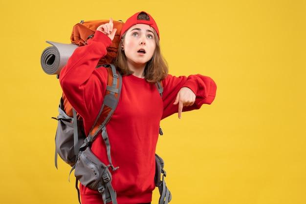 Vorderansicht kühlen weiblichen reisenden mit rucksack, der auf decke und boden zeigt