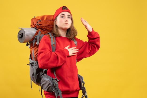 Vorderansicht kühlen weiblichen reisenden mit rucksack, der hand auf ihre brust setzt, die vielversprechend ist