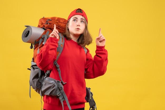 Vorderansicht kühlen weiblichen reisenden mit rucksack, der mit den fingern nach oben zeigt