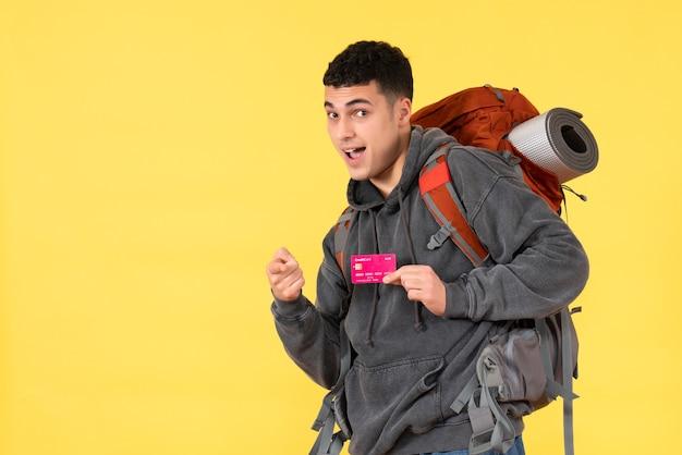 Vorderansicht kühler reisender mann mit rucksack, der kreditkarte hält, die auf kamera zeigt