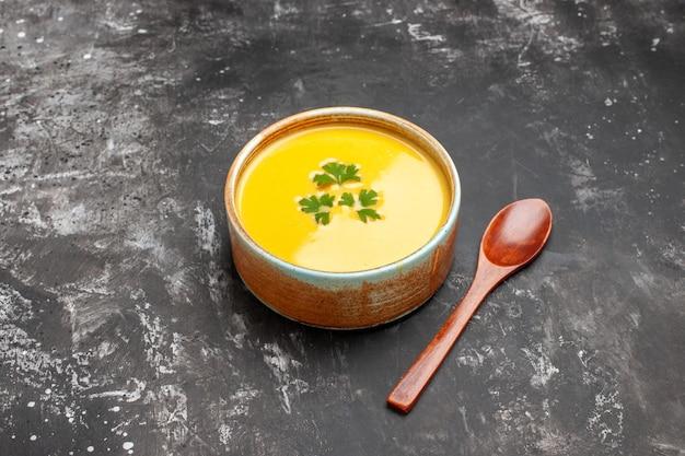 Vorderansicht kürbissuppe mit grüns in der platte auf dunklem tischmahlzeit-fruchtsuppengericht