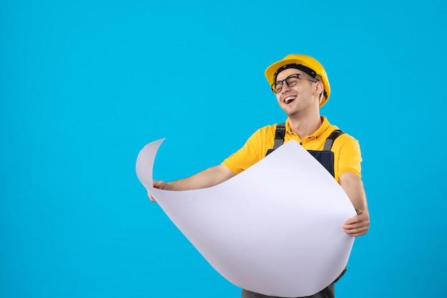 Vorderansicht lachender männlicher baumeister in uniform mit papierplan auf blau
