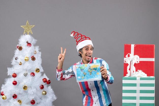 Vorderansicht lachender mann mit spiralfeder-weihnachtsmütze, die siegesfriedenszeichen macht