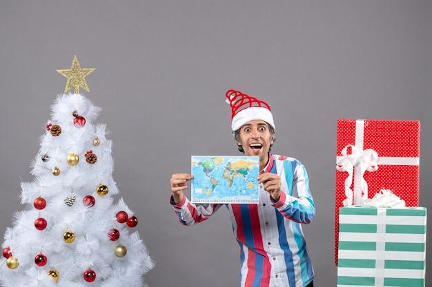 Vorderansicht lachender mann mit weit geöffneten augen, die karte nahe weißem weihnachtsbaum und geschenken mit kopienraum halten Kostenlose Fotos