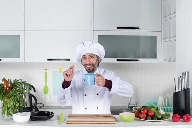 Vorderansicht lächelnder charismatischer koch in uniform, der die tasse hinter dem küchentisch hochhält
