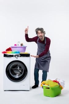Vorderansicht lächelnder haushältermann, der in der nähe einer weißen waschmaschine steht und auf den wäschekorb an der decke auf dem boden zeigt