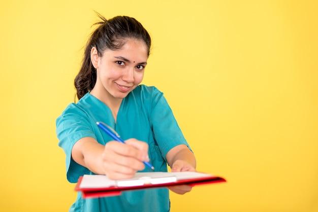 Vorderansicht lächelte junge frau, die zwischenablage und stift auf gelbem hintergrund hält