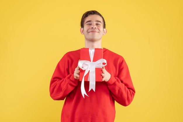 Vorderansicht lächelte junger mann, der auf gelb steht
