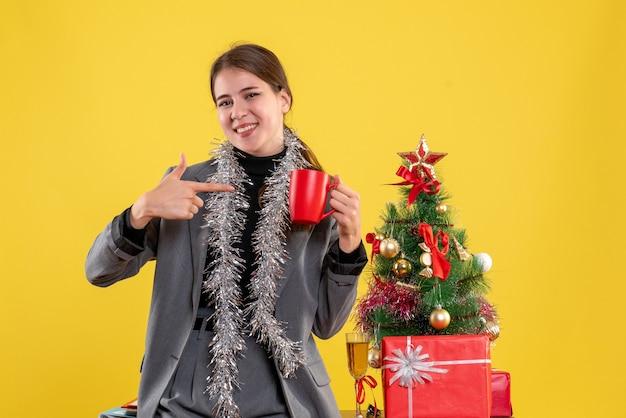 Vorderansicht lächelte junges mädchen, das rote tasse hält, die mit finger selbst nahe weihnachtsbaum und geschenkcocktail zeigt