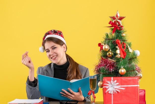 Vorderansicht lächelte junges mädchen mit weihnachtshut, das am tischweihnachtsbaum und geschenkcocktail sitzt