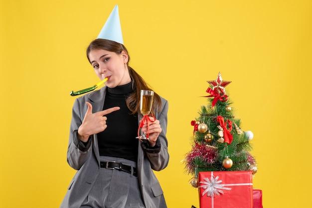 Vorderansicht lächelte mädchen mit partykappe unter verwendung des krachmachers, der nahe weihnachtsbaum und geschenkcocktail röstet