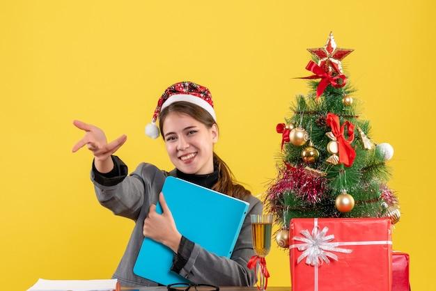 Vorderansicht lächelte mädchen mit weihnachtshut, das am tischweihnachtsbaum und geschenkcocktail sitzt