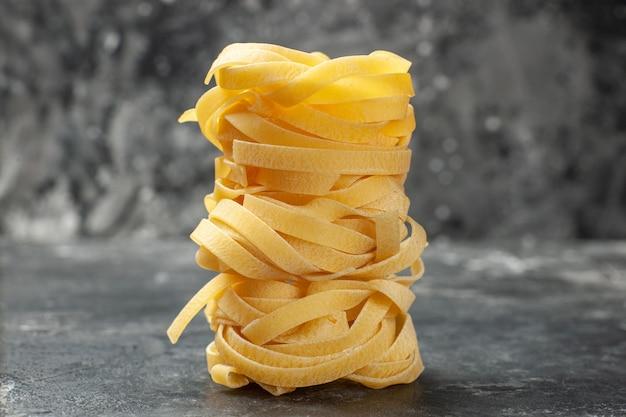 Vorderansicht lange teigstücke auf grauem hintergrund gerollt teig mahlzeit essen pasta dunkelheit küche