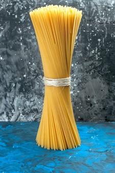 Vorderansicht langes italienisches pasta-rohprodukt, das auf blaulicht-mahlzeit gebunden ist, viele lebensmittelteig-farbfotos