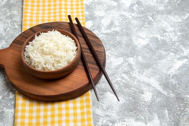 Vorderansicht lecker gekochter reis in brauner platte auf weißem raum