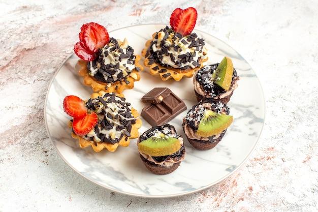 Vorderansicht leckere cremige kuchen kleine desserts für tee mit schokoladenstückchen auf weißem hintergrund obstkuchen sahnekeks kuchentee