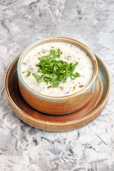 Vorderansicht leckere dovga-joghurtsuppe mit grüns auf einem weißen tischmilchgericht
