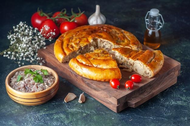 Vorderansicht leckere fleischpastete mit grüns und tomaten auf dunklem hintergrund kekskuchen essen gebäck backen teigfarbe kuchen ofenmahlzeit