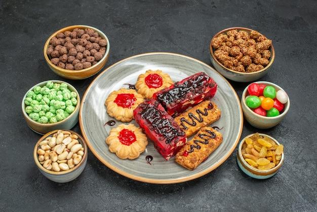Vorderansicht leckere fruchtige kuchen mit keksen und süßigkeiten auf dunklem raum