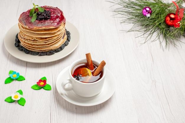 Vorderansicht leckere gelee-pfannkuchen mit rosinen-frucht-gelee und tasse tee auf weißem raum