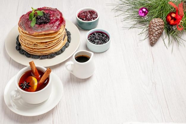 Vorderansicht leckere geleepfannkuchen mit rosinen und tasse tee auf weißem raum