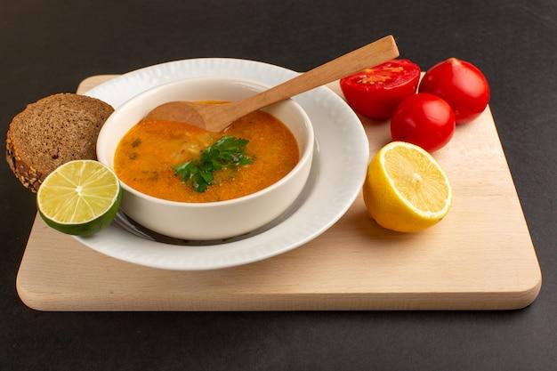 Vorderansicht leckere gemüsesuppe in teller mit brotlaib zitronentomaten auf dunklem schreibtisch.