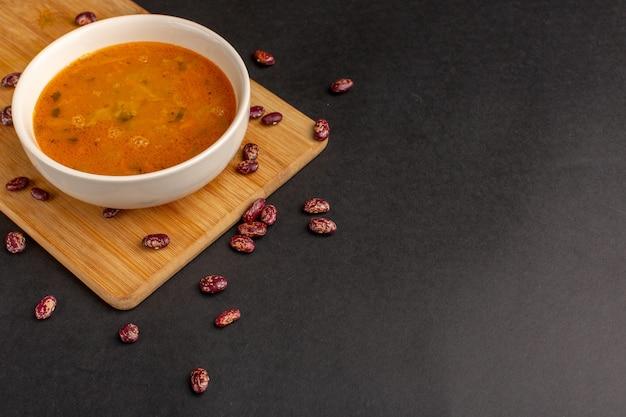 Vorderansicht leckere gemüsesuppe in teller zusammen mit rohen bohnen auf dem dunklen schreibtisch.