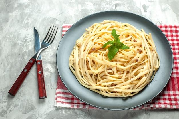 Vorderansicht leckere italienische pasta mit besteck auf weißem mehlteig fotofarbgericht essen