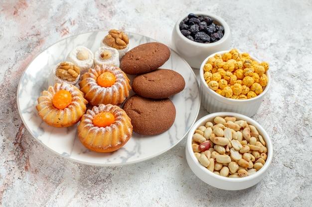 Vorderansicht leckere kekse mit süßigkeiten und nüssen auf weißem raum