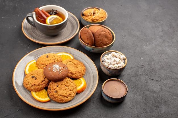 Vorderansicht leckere kekse mit tasse tee und orangen auf dunklem hintergrund keksfrucht süßer kuchen keks zitrus