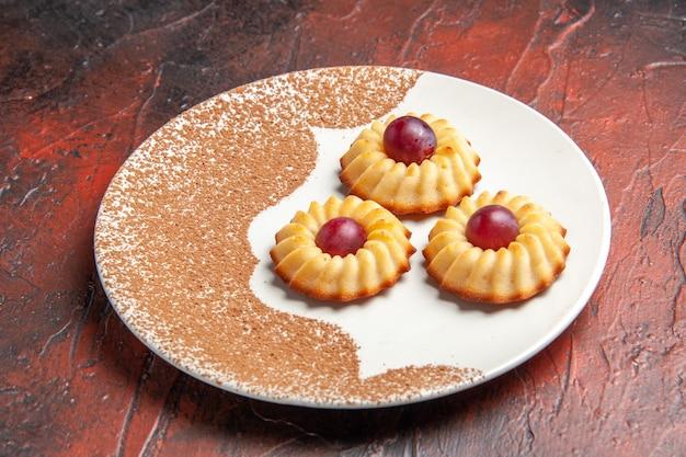 Vorderansicht leckere kleine kekse innerhalb platte auf dunklem tisch süßer kekskuchen