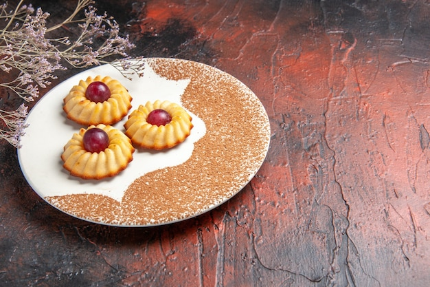 Vorderansicht leckere kleine kekse innerhalb platte auf dunklen tischkuchen süße kekse