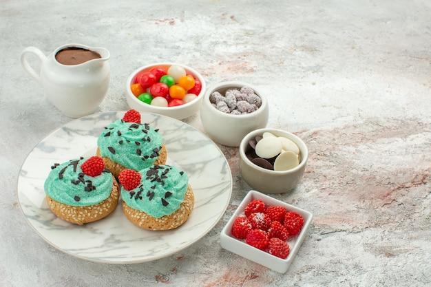 Vorderansicht leckere kleine kuchen mit bunten bonbons und keksen auf weißem hintergrund dessertkuchen kuchen regenbogenfarben süßigkeiten