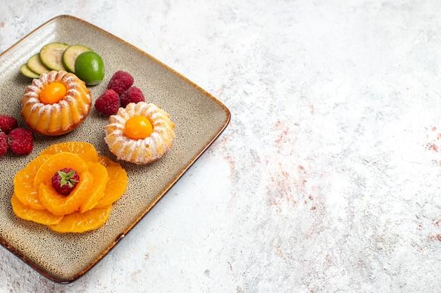 Vorderansicht leckere kleine kuchen mit geschnittenen früchten auf weißem schreibtisch keks zuckerkuchen tee süße tortenfrucht