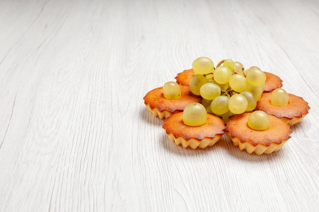 Vorderansicht leckere kleine kuchen mit trauben auf weißem schreibtisch teekuchenkuchen süßer dessertkeks