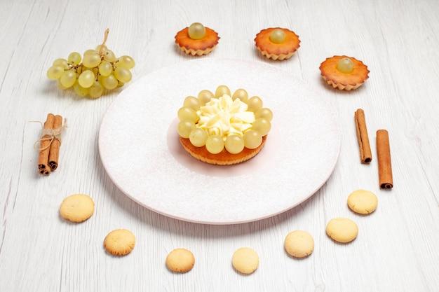 Vorderansicht leckere kleine kuchen mit trauben und keksen auf weißem hintergrund dessert keks tee kuchen kuchen süße kekse
