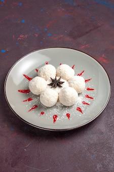 Vorderansicht leckere kokosbonbons mit rotem zuckerguss auf dunklem raum