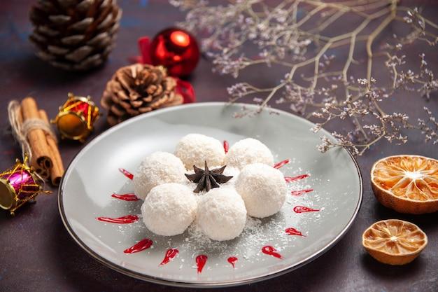 Vorderansicht leckere kokosbonbons rund geformt mit rotem zuckerguss auf dunklem raum