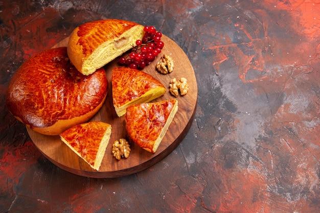 Vorderansicht leckere kuchen geschnitten mit roten beeren auf dem dunklen tischgebäckkuchen kuchen süß