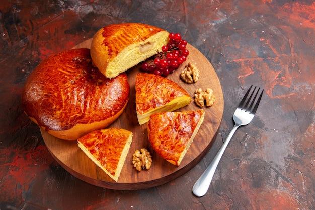Vorderansicht leckere kuchen geschnitten mit roten beeren auf dunklem schreibtisch gebäckkuchen kuchen süß