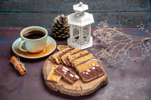 Vorderansicht leckere kuchenscheiben mit nüssen und tasse tee auf dunklem raum