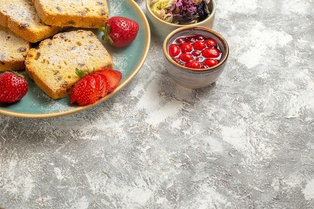 Vorderansicht leckere kuchenstücke mit erdbeeren auf leichter oberfläche früchte süße kuchen torte